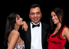 Flirting with girls. 40 something executive with tuxedo flirting with young girls Stock Photos