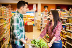 Flirting at the grocery store. Cute couple flirting and having fun while doing some shopping at the supermarket royalty free stock image
