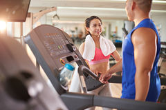 Flirting in gym. Young Asian women flirting with sportsman in gym stock photos