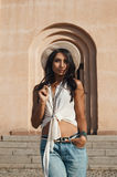 Flirting indian lady in casual summer outfit against ancient building. Royalty Free Stock Images