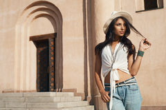 Flirting lady in casual summer outfit against ancient building. Stock Photos