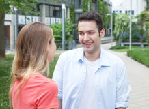 Flirting latin couple. Outside in a park on the campus with meadow and trees in the background Royalty Free Stock Photography