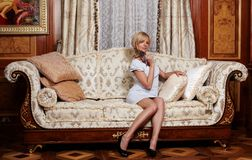 Flirting maid  in luxury hotel. Flirting maid sitting on a sofa in luxury hotel Royalty Free Stock Photography