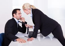 Flirting in the office. As a beautiful blonde businesswoman pulls a colleague towards her by his tie stock photos