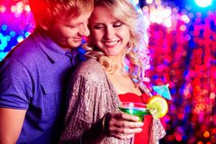 Flirting at party. Young couple flirting at party against sparkling background stock photography