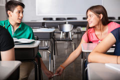 Flirting and passing love notes. Cute couple of teens exchanging love notes and flirting in a classroom Royalty Free Stock Photo