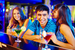 Flirting. Portrait of pretty girl flirting with guy at party in the bar stock image