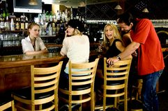 Flirting at the pub. Young girls on a night out have fun, chat with the bartender, while a handsome guy comes around to say hi Royalty Free Stock Photography