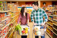 Flirting at the supermarket. Young men and a women flirting at the supermarket while they do their shopping stock photography