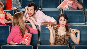 Flirting in The Theater. Man flirting with girl next to embarrassed friend in theater stock images