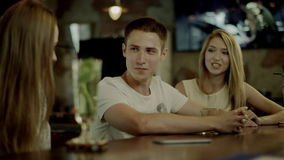 Flirting with two women in a bar. Young man flirting with two women at a bar counter in a bar stock footage