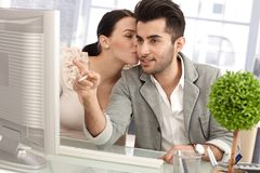 Flirting in workplace. Young colleagues flirting in workplace, women kissing men while working together stock images