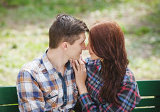 Flirting young couple on a bench. Flirting young couple with closed eyes in plaid shirts sitting on a bench in the park Stock Photos