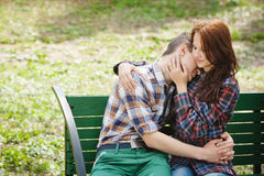 Flirting young couple on a bench. Flirting and hugging young couple in plaid shirts sitting on a bench in the park Stock Image