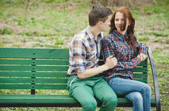 Flirting young couple on a bench. Flirting young couple in plaid shirts sitting on a bench in the park Royalty Free Stock Photography