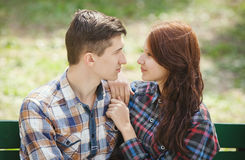 Flirting young couple on a bench. Flirting young couple sitting on a bench in the park and looking into each other`s eyes Royalty Free Stock Photography