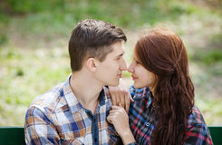 Flirting young couple on a bench. Flirting young couple sitting on a bench in the park and looking into each other`s eyes Stock Image