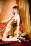 Flirting young woman in golden dress Royalty Free Stock Photos