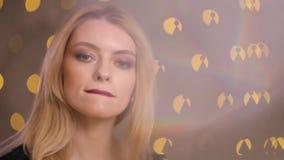 Flirtvrouw het flirten het stellen op een camera, langzame motie, gele bokehachtergrond stock video