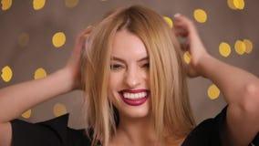 Flirtvrouw het flirten het stellen op een camera, langzame motie, gele bokehachtergrond stock videobeelden