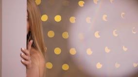 Flirtvrouw het stellen op een camera, langzame motie, gele bokehachtergrond stock footage