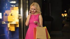Flirty ξανθό έχοντας τη τηλεφωνική συνομιλία, πολυτέλεια που ψωνίζει στη μπουτίκ μόδας απόθεμα βίντεο