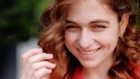 Flirty που χαμογελά την ντροπαλή γυναίκα που παίζει τη σγουρή τρίχα πιπεροριζών απόθεμα βίντεο