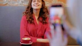 Flirty усмехаясь женщина представляя фото отдыха мобильное акции видеоматериалы