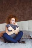 Flirty attraktive gelockte Frau, die auf dem Bett umarmt Kissen sitzt Lizenzfreie Stockbilder