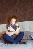Flirty attraktivt lockigt kvinnasammanträde på säng som kramar kudden Royaltyfria Bilder