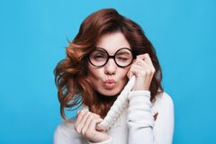 Flirty beauty. Attractive young woman winking and kissing while standing against blue background stock photography