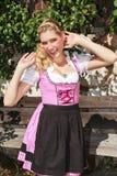 Flirty blond bavarian girl in dirndl Royalty Free Stock Images