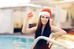 Flirty Christmas Woman with Cocktail at the Pool. Attractive girl celebrating Christmas in a spa resort Stock Images