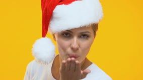 Flirty dam i den Santa Claus hatten som överför luftkyssen till kameran, ferieunderhållning arkivfilmer