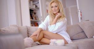 Flirty Frau, die auf dem Wohnzimmer-Sofa sich lehnt Lizenzfreies Stockfoto