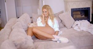 Flirty Frau, die auf dem Wohnzimmer-Sofa sich lehnt Lizenzfreie Stockfotografie