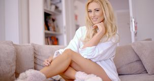 Flirty Frau, die auf dem Wohnzimmer-Sofa sich lehnt Stockbild