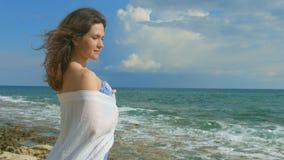 Flirty geheimzinnige vrouw die zich alleen op kust bevinden, die van mooie overzeese mening genieten stock footage