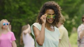 Flirty girl with curly hair dancing, smiling to camera. Friends partying in park