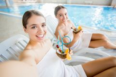 Happy vacation. Flirty girls with coconut drinks sitting on deckchairs by swimming-pool Royalty Free Stock Photos