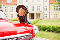 Flirty and glamorous woman with red retro car Royalty Free Stock Photo