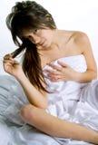 Flirty junge Frau abgedeckt durch Bett-Blatt Lizenzfreie Stockfotografie