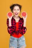 Flirty lächelnde Frau, die mit Hälften der Pampelmuse blinzelt und aufwirft Stockfotos