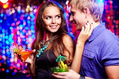 Flirty look. Girl with a cocktail attracting the attention of her boyfriend with a flirtatious look and tender touch Stock Photos