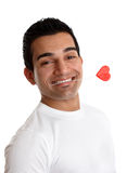 Flirty man holds love heart between teeth Royalty Free Stock Photos