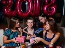 Flirty New 2018 Year party. Females attention for macho man, Christmas gifts for young male. Romantic mood at celebration, happiness concept royalty free stock image