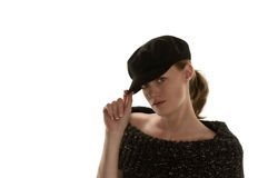 Flirty newsboy hat. Close-up of a caucasian female tilting down a black newsboy hat over her face wearing an off the shoulders black knitted top in front of a Stock Photography