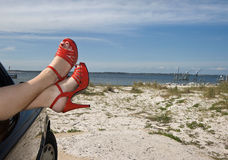 Flirty Red Shoes at the Beach. Woman's legs with red patent leather spike heels dangling out the car window parked at the beach royalty free stock image