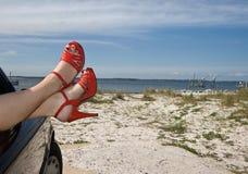 Flirty rote Schuhe am Strand Lizenzfreies Stockbild