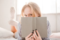 Flirty shy young woman covered her face by the book Royalty Free Stock Photography